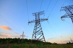 Mire para arriba el alto voltaje de las torres del powertransmission Fotos de archivo libres de regalías
