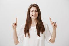 Mire para arriba no abajo Retrato de la mujer europea encantadora positiva con sonrisa brillante que destaca en el techo con índi Fotos de archivo libres de regalías