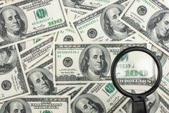 Mire a través de una lupa en el dinero Fotografía de archivo libre de regalías