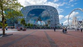 Mire a través desde fuera del pasillo del mercado en Rotterdam Una noria al lado del edificio y la gente y los ciclistas imagen de archivo