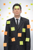 Mired in work. Frustrated businessman covered with the adhesive Royalty Free Stock Image