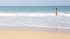MIRISSA,斯里兰卡- 2014年3月:妇女输入的海看法波浪的在Mirissa 这个小含沙热带海滩吹嘘一些o 股票录像