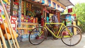 MIRISSA, ШРИ-ЛАНКА - МАРТ 2014: Велосипед припаркованный вне местного магазина при человек стоя в предпосылке на улице в Mirissa сток-видео