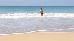 MIRISSA, SRI LANKA - MÄRZ 2014: Ansicht von hereinkommendem Meer der Frau in den Wellen in Mirissa Dieser kleine sandige tropisch stock video