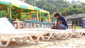 MIRISSA, SRI LANKA - MÄRZ 2014: Bemannen Sie das Vorbereiten von Sonnenbetten für Touristen auf Strand in Mirissa Leben dieses St stock video