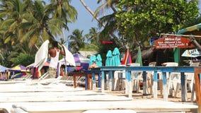 MIRISSA, SRI LANKA - MÄRZ 2014: Bemannen Sie das Vorbereiten von Sonnenbetten für Touristen auf Strand in Mirissa Leben dieses St stock footage