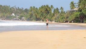 MIRISSA, SRI LANKA - MÄRZ 2014: Bemannen Sie Stellung in den Wellen, die oben auf Ufer in Mirissa sich waschen Dieser kleine sand stock footage