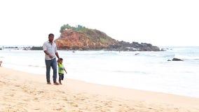 MIRISSA, SRI LANKA - MÄRZ 2014: Lokaler Mann und Sohn, die hinunter den sandigen Strand von Mirissa geht Dieser kleine sandige tr stock footage