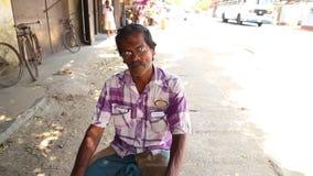 MIRISSA, SRI LANKA - MÄRZ 2014: Porträt des älteren Mannes mit den Schauspielen, die auf den Straßen von Mirissa sitzen stock footage