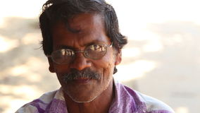 MIRISSA, SRI LANKA - MÄRZ 2014: Porträt des älteren Mannes mit den Schauspielen, die auf den Straßen von Mirissa sitzen stock video footage