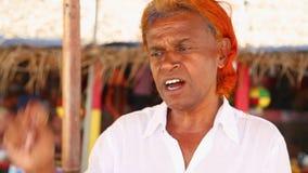 MIRISSA, SRI LANKA - MÄRZ 2014: Porträt des lokalen Verkäufers versuchend, aufpassende Ausflüge des Wals an Touristen zu verkaufe stock video