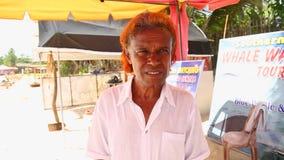 MIRISSA, SRI LANKA - MÄRZ 2014: Porträt des lokalen Verkäufers versuchend, aufpassende Ausflüge des Wals an Touristen zu verkaufe stock footage