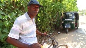 MIRISSA, SRI LANKA - MÄRZ 2014: Porträt eines lokalen Mannes auf der Straße mit Fahrrad in Mirissa Fahrräder sind eine sehr billi stock video footage