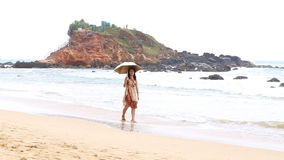 MIRISSA, SRI LANKA - MARCH 2014: Japanese tourist walking down beach with umbrella as sun protection. This small sandy tropical be stock video footage