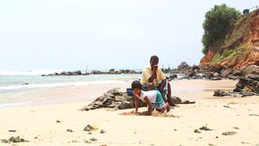 MIRISSA, SRI LANKA - MARCH 2014: Little girl playing on the beach in Mirissa. This small sandy tropical beach boasts some of Sri L stock video footage