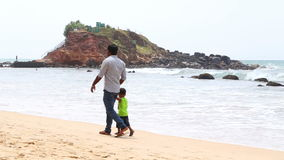MIRISSA, SRI LANKA - MARCH 2014: Local father and daughter walking down the beach. This small sandy tropical beach boasts some of  stock footage