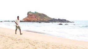 MIRISSA, SRI LANKA - MARCH 2014: Local man walking down the sandy beach of Mirissa. This small sandy tropical beach boasts some of stock video footage