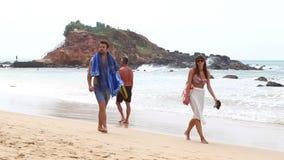 MIRISSA, SRI LANKA - MARCH 2014: Tourists walking up and down the sandy beach of Mirissa. This small sandy tropical beach boasts s stock footage