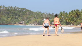 MIRISSA, SRI LANKA - MARCH 2014: The view of a beach in Mirissa with people passing by. This small sandy tropical beach boasts som stock footage