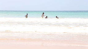 MIRISSA, SRI LANKA - MARCH 2014: The view of a five local boys enjoying in the ocean in Mirissa. This small sandy tropical beach b stock footage