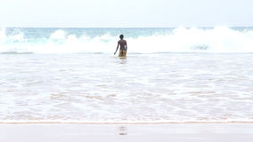 MIRISSA, SRI LANKA - MARCH 2014: The view of a five local boys enjoying in the ocean in Mirissa. This small sandy tropical beach b stock video footage