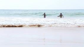 MIRISSA, SRI LANKA - MARCH 2014: The view of a three local boys enjoying in the ocean in Mirissa. This small sandy tropical beach  stock video