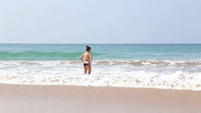 MIRISSA, SRI LANKA - MARCH 2014: View of woman entering sea in the waves in Mirissa. This small sandy tropical beach boasts some o. F Sri Lanka�s best and most stock video