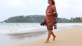 MIRISSA, SRI LANKA - MARCH 2014: Woman in sarong around her shoulders walking down the beach. This small sandy tropical beach boas stock video footage