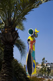 Miro Sculpture in Barcelona. Sculpture in Barcelona called Woman and Bird by Joan Miro framed by a palm tree Stock Photography