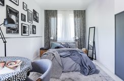 Miroir à côté de lit avec des feuilles dans l'intérieur de chambre à coucher avec la lampe et les affiches noires Photo r?elle photographie stock
