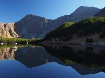 Miroir bleu du lac dans le coucher du soleil dans les montagnes Image stock