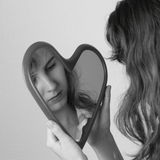 Miroir de coeur avec le visage de filles Images stock