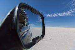 Miroir de voiture avec la vue des appartements impressionnants de sel d'Uyuni avec le cle Photos stock