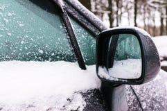 Miroir de vue arrière droit et fenêtre latérale de la voiture couverte de neige photographie stock