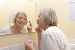 Miroir mûr heureux de crème hydratante de femme Photo libre de droits