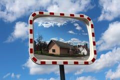 Miroir rectangulaire convexe du trafic monté sur le poteau en métal avec le voisinage et la route par réflexion sur le fond nuage images libres de droits