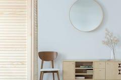 Miroir rond au-dessus de chaise en bois et armoire dans le vestibule minimal intérieur avec le décor image libre de droits