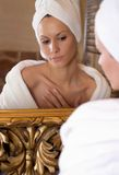 At the mirror. Beautiful girl is getting ready in front of the mirror royalty free stock images