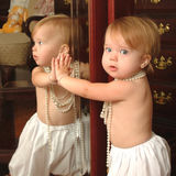 Mirror. Baby in bloomers and beads reflected in mirror Royalty Free Stock Photography