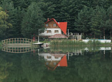 Mirror. House in forest looks interesting in water Royalty Free Stock Photos