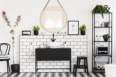 Mirror above black washbasin in white bathroom interior with chair and flowers. Real photo. Concept royalty free stock photo