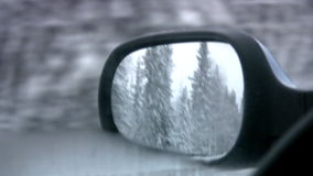 Mirror of a back kind. Kind in the left mirror of a back kind of car on a wood covered with snow and lake, covered by ice during movement on a winter road stock video footage