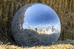 Mirror Ball From A Disco Lies On A Straw Outdoors Royalty Free Stock Image