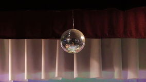 Mirror ball reflects white light. Disco ball with reflected moving rays stock footage