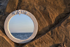 Mirror at the beach. Mirror with white frame on a rock reflecting beach royalty free stock photo