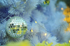 Mirror Christmas ball items on white pie and yellow bokeh form LED lighting background. Stock Images