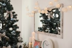 Mirror with Christmas lights on wall and fir tree in stylish living room. Mirror with Christmas lights on wall and decorated fir tree in stylish living room stock images