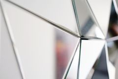 Abstract mirror. Close-up. Mirror with crystals in wall, decoration and reflection. Abstract glass background. Polygonal surface. Close-up royalty free stock images