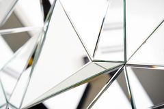 Mirror with crystals in wall, decoration and reflection. Abstract glass background. Polygonal surface. Close-up. Texture royalty free stock photo