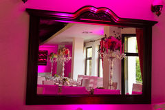 Mirror with dinner table at the wedding. This image shows a mirror with dinner table at the wedding with purple lights Stock Images